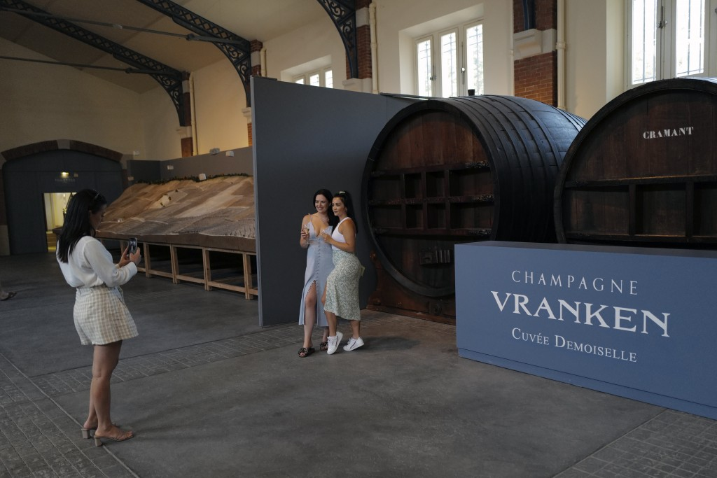 Visitors from London, take photos with a glass of Champagne as they visit the Vranken-Pommery Monopole in Reims, the Champagne region, east of Paris, ...