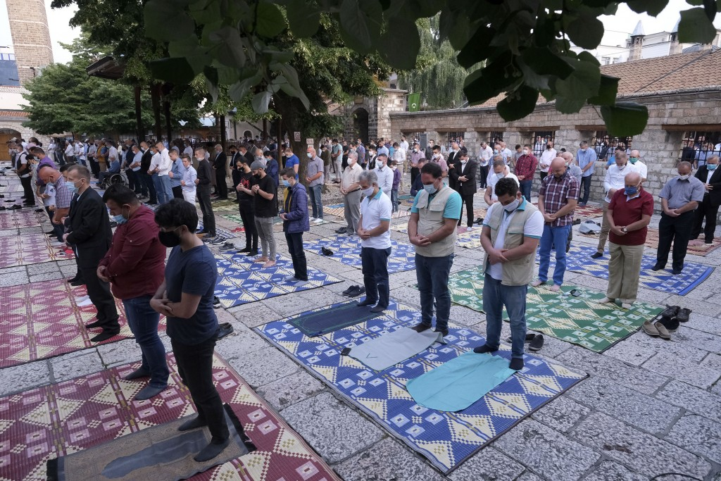 Worshippers wearing masks to help stop the spread of the coronavirus, offer Eid al-Adha prayer while maintaining a social distance in front of the Gaz...