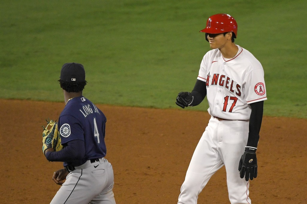 Los Angeles Angels' Shohei Ohtani, right, of Japan, gestures to Seattle Mariners' Shed Long Jr. after stealing second during the seventh inning of a b...