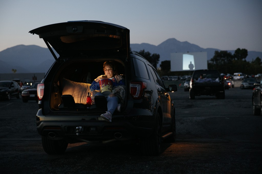 FILE - Serena Benavidez looks at her smartphone while waiting for a movie to start at Mission Tiki drive-in theater in Montclair, Calif., on May 28, 2...