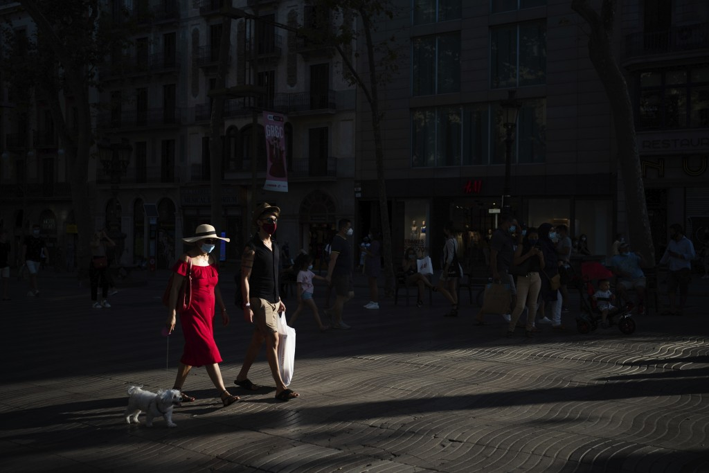 People wearing face masks walk along Las Ramblas in Barcelona, Spain, Monday, July 27, 2020. Britain has put Spain back on its unsafe list and announc...