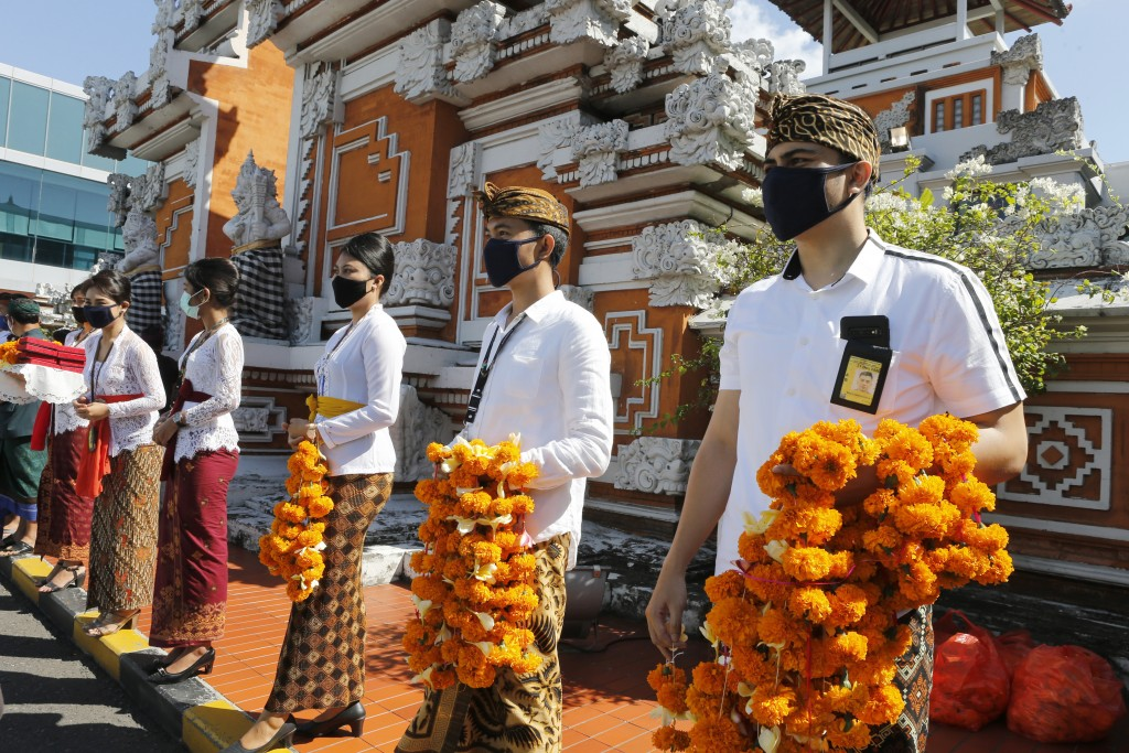 Airport officers wearing face masks line up as they hold flowers to welcome passengers at Bali airport, Indonesia on Friday, July 31, 2020. Indonesia'...
