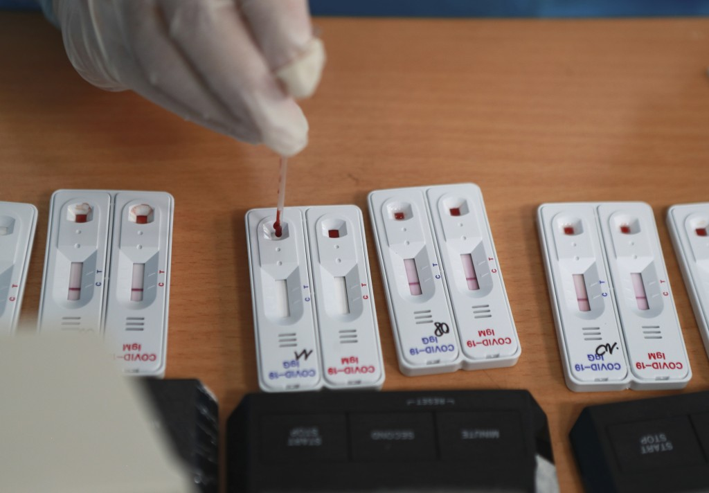 A health worker drops drawn blood on a test kit of COVID-19 in Hanoi, Vietnam, Friday, July 31, 2020. Vietnam reported on Friday the country's first d...