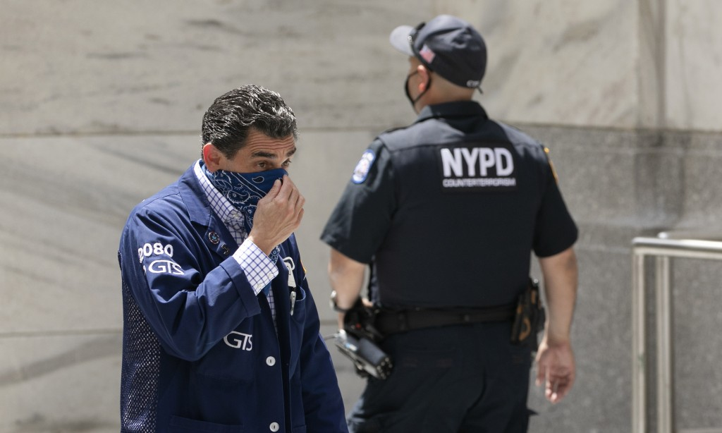 A stock trader, left, adjusts his mask as he enters the New York Stock Exchange, Thursday, July 30, 2020. Stocks are falling on Wall Street Thursday a...