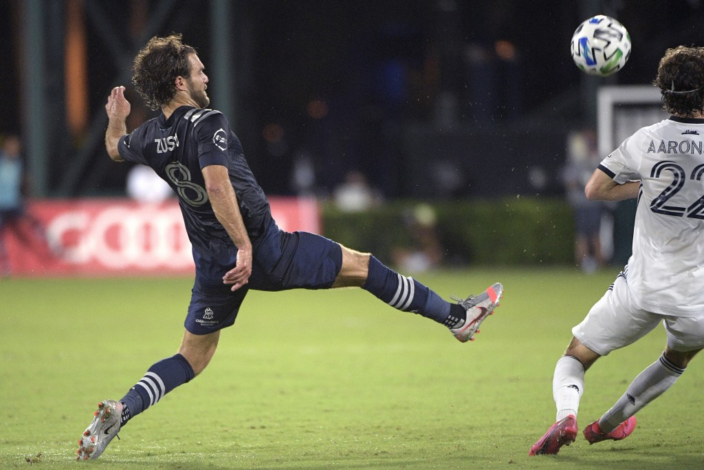 Sporting Kansas City midfielder Graham Zusi (8) makes a pass in front of Philadelphia Union midfielder Brenden Aaronson (22) during the first half of ...