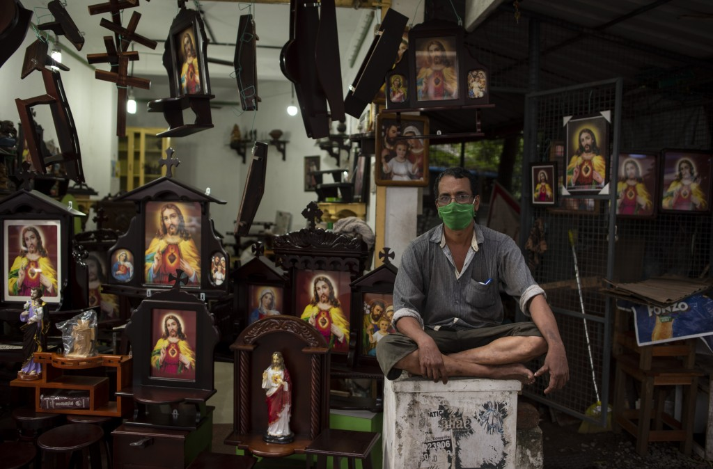 Josy, a man who sells images of Jesus Christ, wears a mask as a precaution against the coronavirus as he waits for customers in Kochi, Kerala state, I...