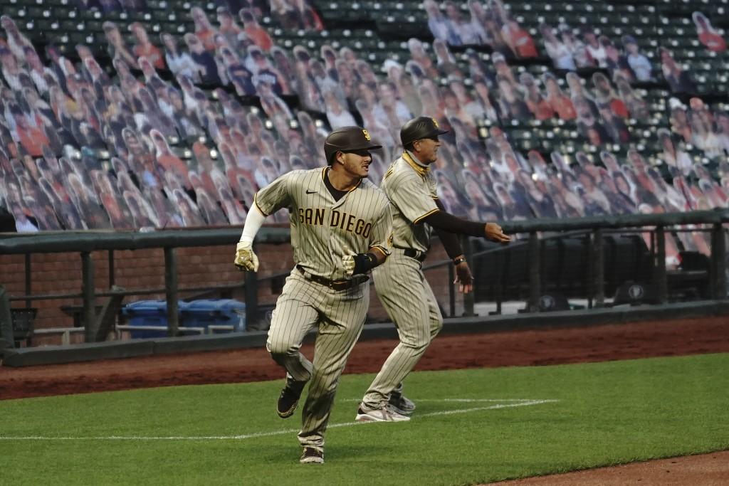 San Diego Padres' Manny Machado, left, runs toward home in front of third base coach Glenn Hoffman to score against the San Francisco Giants during th...