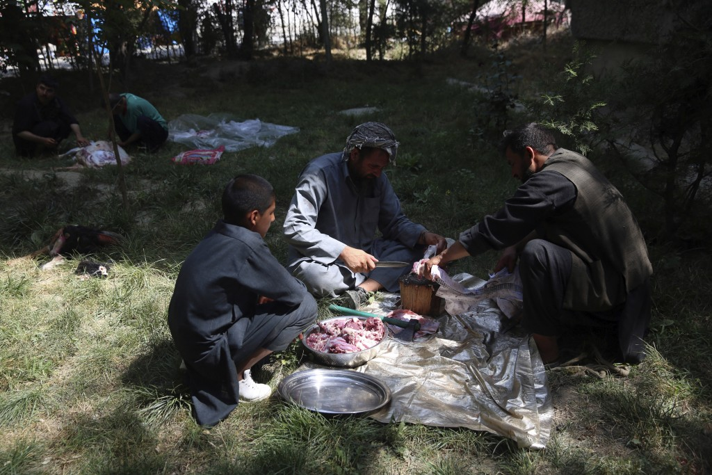 Men slaughter sheep on the first day of Eid al-Adha in Kabul, Afghanistan, Friday, July 31, 2020. During Eid al-Adha, or Feast of Sacrifice, Muslims s...
