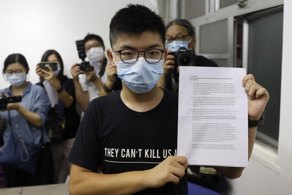 Hong Kong pro-democracy activist Joshua Wong shows his disqualification notice during a press conference in Hong Kong, Friday, July 31, 2020. On Thurs...