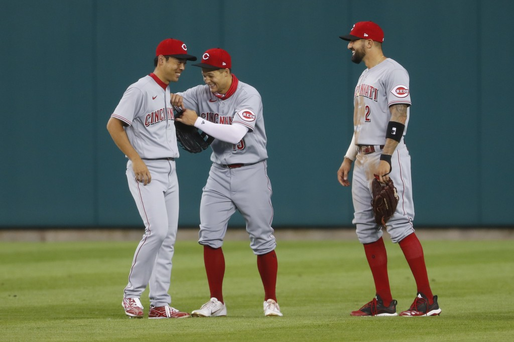 Cincinnati Reds outfielders Shogo Akiyama, from left, Nick Senzel (15) and Nicholas Castellanos (2) laugh together during a break in play in the seven...