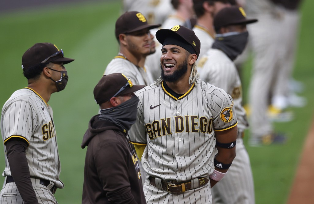 San Diego Padres shortstop Fernando Tatis Jr. jokes with teammates as they line up for introductions before a baseball game against the Colorado Rocki...