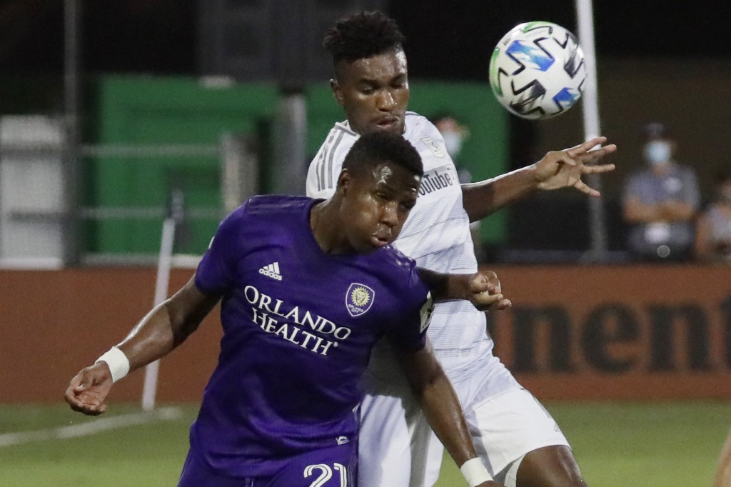 Orlando City midfielder Andres Perea (21) hits the ball as Los Angeles FC midfielder Jose Cifuentes (11) closes in during the second half of an MLS so...
