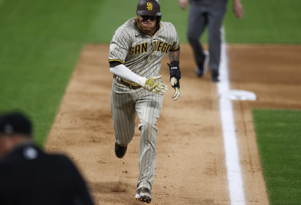 San Diego Padres' Manny Machado advances from third base to score on a passed ball against the Colorado Rockies in the sixth inning of a baseball game...