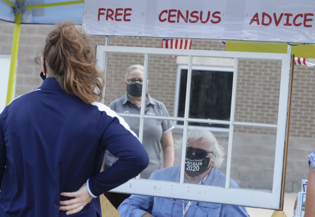 Amid concerns of the spread of COVID-19, census worker Ken Leonard wears a mask as he mans a U.S. Census walk-up counting site set up for Hunt County ...