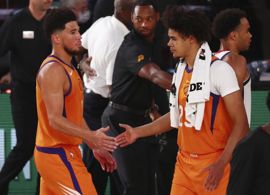 Phoenix Suns guard Devin Booker (1) slaps hands with forward Cameron Johnson (23) after defeating the Washington Wizards in an NBA basketball game in ...