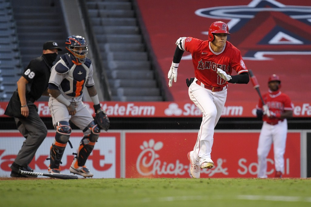 Los Angeles Angels' Shohei Ohtani, right, runs to first as he grounds out while Houston Astros catcher Martin Maldonado, center, and home plate umpire...