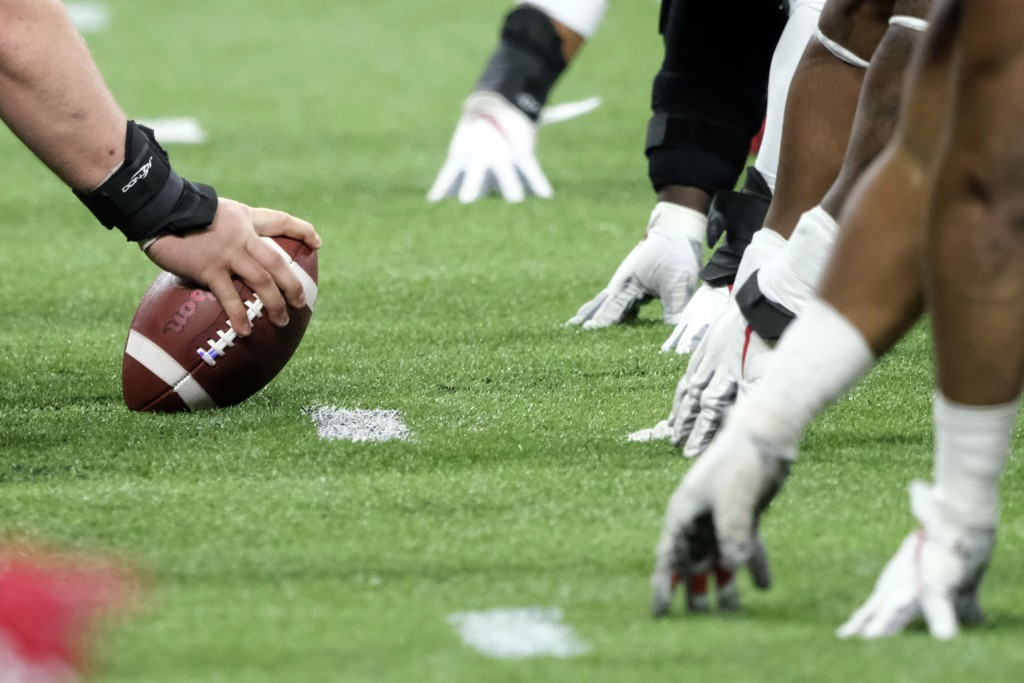 FILE - In this Dec. 7, 2019, file photo, a player prepares to hike the ball at the line of scrimmage during the first half of the Big Ten championship...