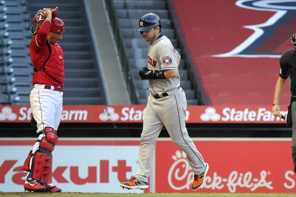 Houston Astros' Josh Reddick, right, scores as Los Angeles Angels catcher Jason Castro watches after George Springer was walked with the bases loaded ...