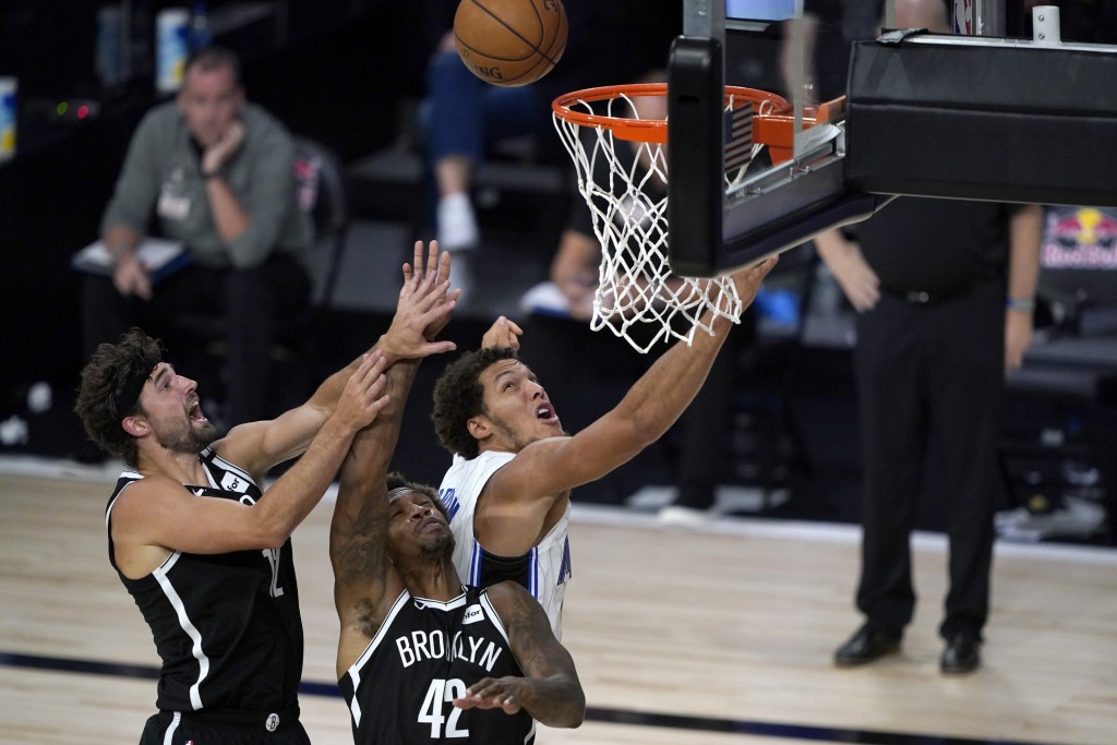 Orlando Magic's Aaron Gordon, right, watches a rebound with Brooklyn Nets' Lance Thomas (42) and Joe Harris, left, during the second half of an NBA ba...