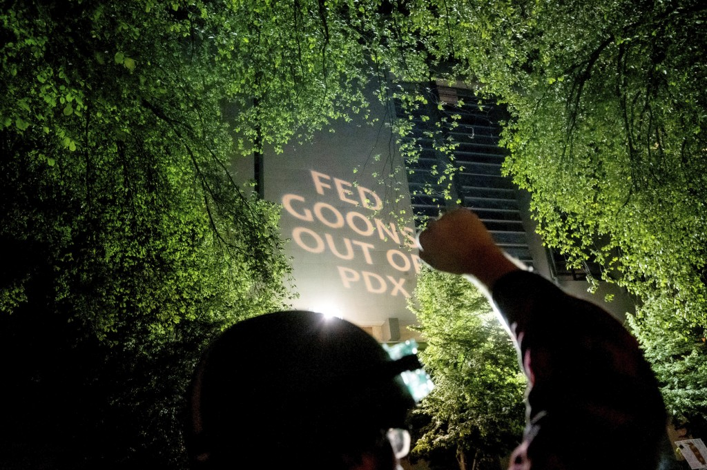 A Black Lives Matter protester raises his fist as text is projected onto the Mark O. Hatfield United States Courthouse on Friday, July. 31, 2020, in P...