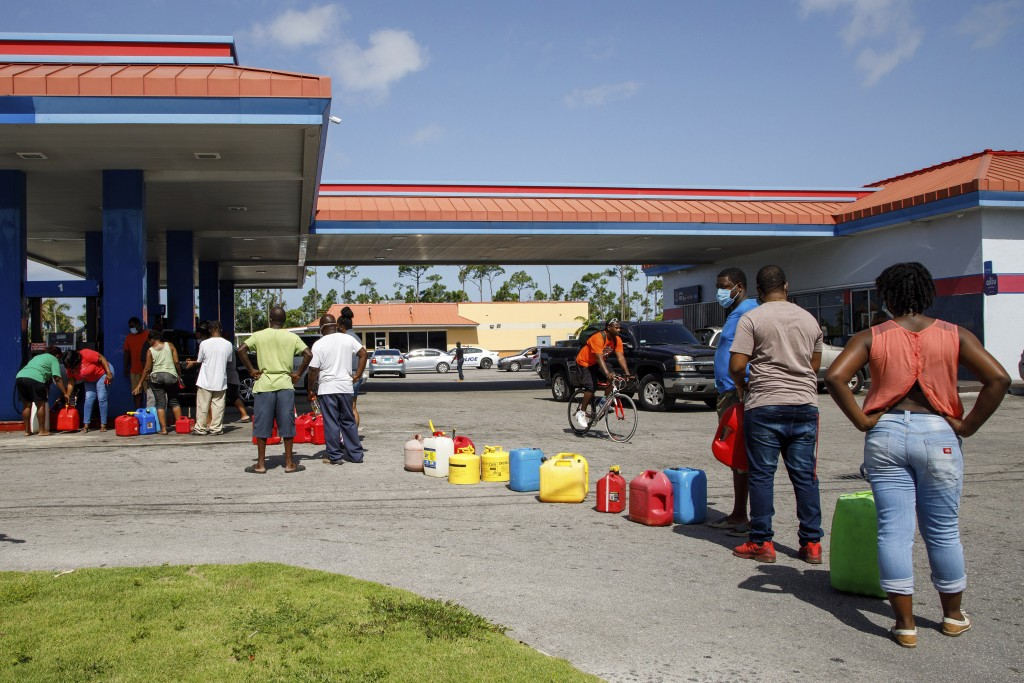 Residents wait in line to fill their containers with gasoline before the arrival of Hurricane Isaias in Freeport, Grand Bahama, Bahamas, Friday, July ...
