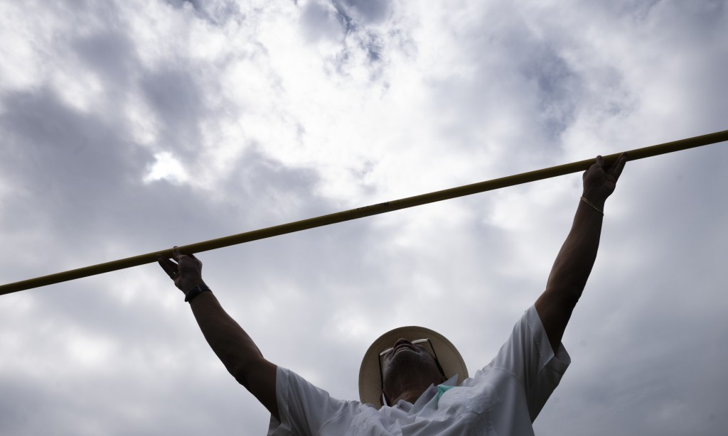Benn Fields holds a high jump crossbar over his head, Friday, July 31, 2020, at his home in Salisbury Mills, N.Y. Fields will forever be known as a U....