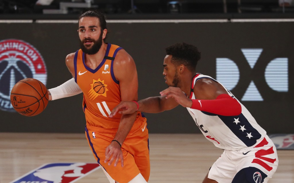 Phoenix Suns guard Ricky Rubio (11) is defended by Washington Wizards forward Troy Brown Jr. (6) during the second half of an NBA basketball game Frid...