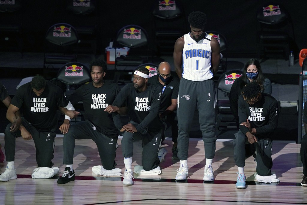 Orlando Magic's Jonathan Isaac (1) stands as others kneel before the start of an NBA basketball game between the Brooklyn Nets and the Orlando Magic F...
