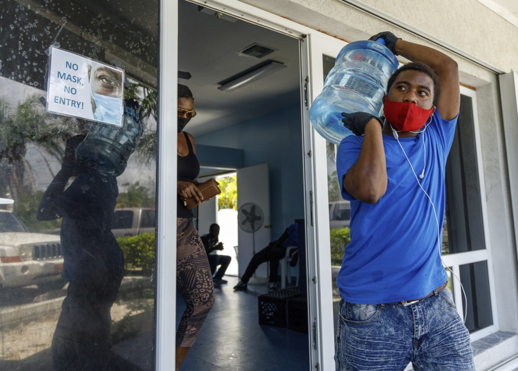 A man carries drinking water for a customer at a water depot store before the arrival of Hurricane Isaias in Freeport, Grand Bahama, Bahamas, Friday, ...