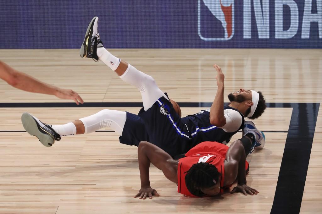 Dallas Mavericks' Seth Curry, top, falls atop of Houston Rockets' Danuel House Jr., bottom, during the first half of an NBA basketball game Friday, Ju...