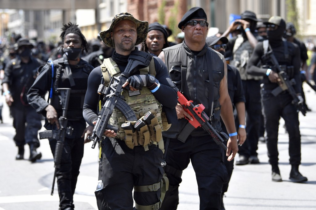 """Armed members of the """"NFAC"""" march through downtown Louisville, Ky., toward the Hall of Justice on Saturday, July 25, 2020. Hundreds of activists deman..."""