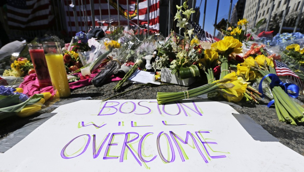 FILE - In this April 17, 2013 photograph, flowers and signs adorn a barrier, two days after two explosions killed three and injured hundreds, at Boyls...