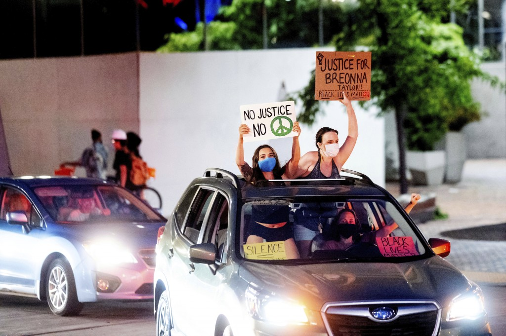 Black Lives Matter protesters hold signs during a caravan on Friday, July 31, 2020, in Portland, Ore. Following an agreement between Democratic Gov. K...