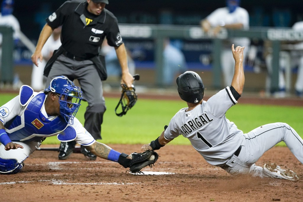 Chicago White Sox's Nick Madrigal (1) is tagged out by Kansas City Royals catcher Salvador Perez as he tried to score on a single hit by Leury Garcia ...