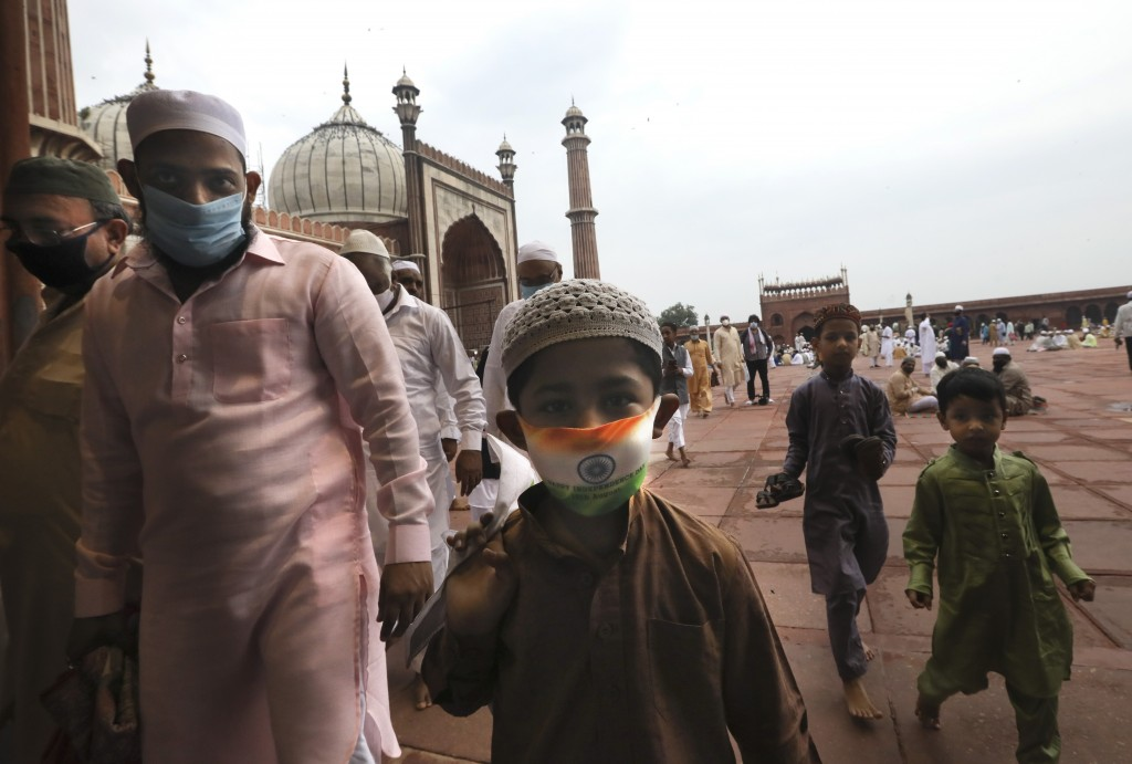 An Indian Muslim boy wears a protective mask in the colors of the Indian national flag, leaves  after offering Eid al-Adha prayer at the Jama Masjid i...