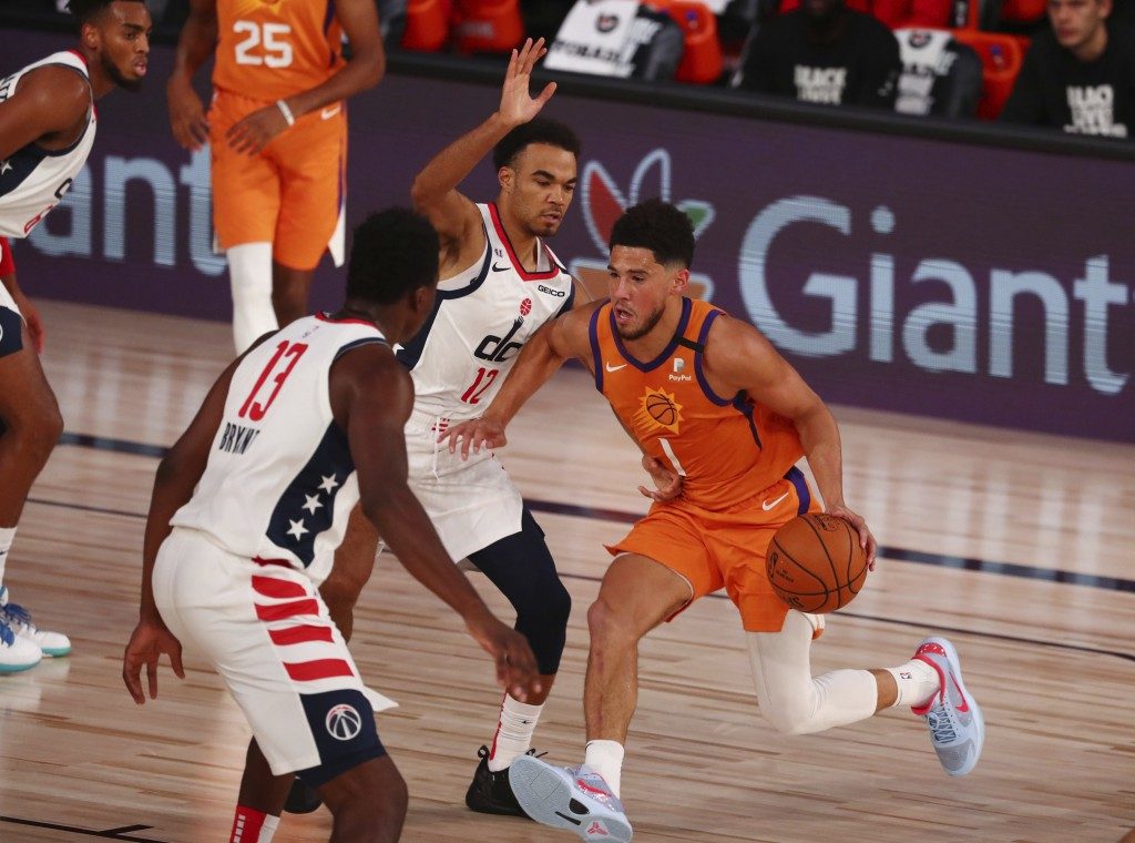 Phoenix Suns guard Devin Booker (1) drives to the basket against Washington Wizards guard Jerome Robinson (12) in the first half an NBA basketball gam...