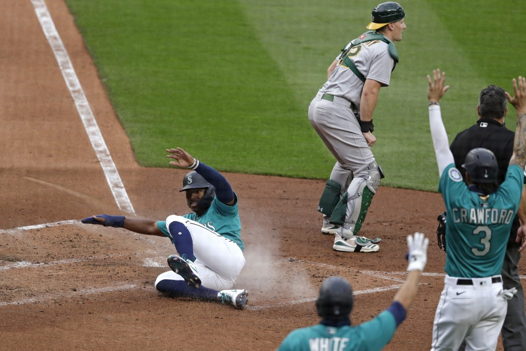 Seattle Mariners' Kyle Lewis slides safely home to score as Oakland Athletics catcher Sean Murphy waits for the ball in the fourth inning of a basebal...