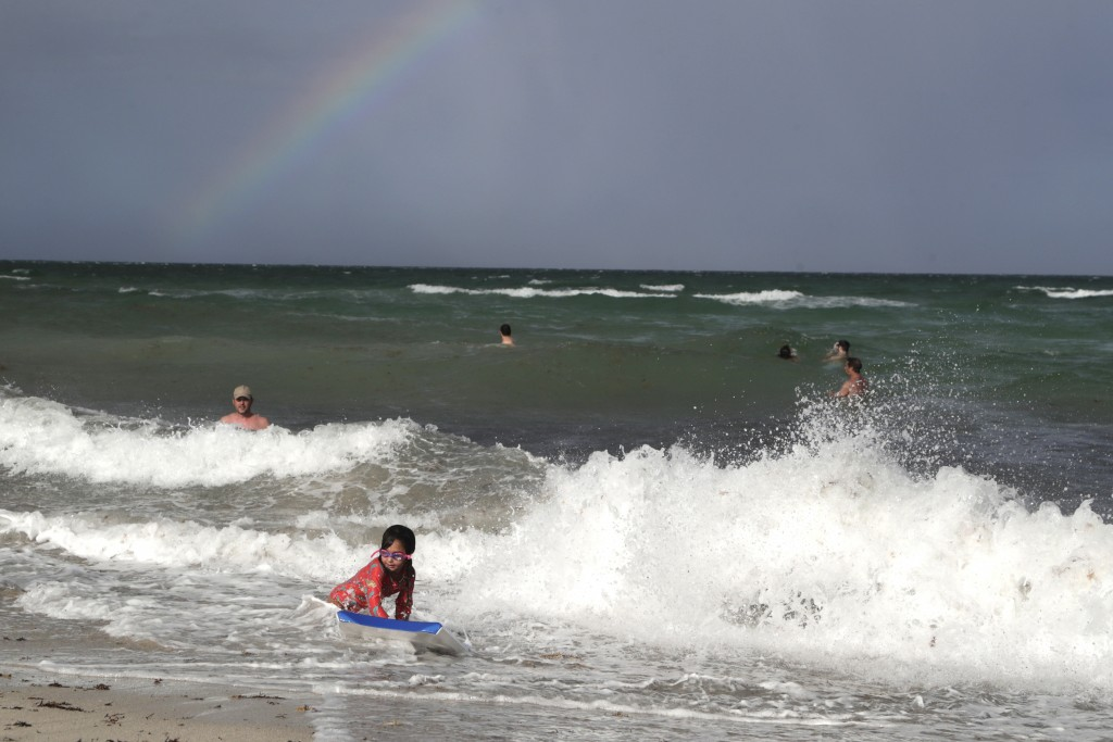 A rainbow is seen on the horizon as people enjoy the waves from a high surf, Friday, July 31, 2020, in Miami Beach, Fla. Forecasters declared a hurric...