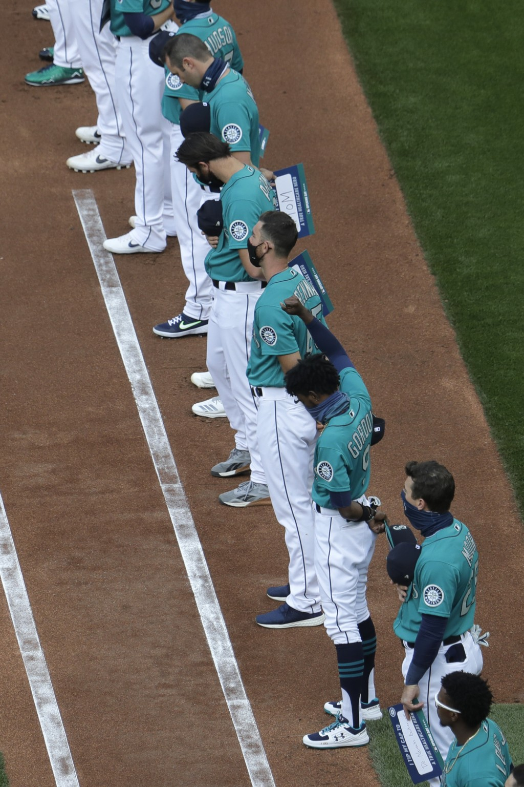 Seattle Mariners left fielder Dee Gordon (9) raises his fist during the singing of the national anthem before the Mariners' home opener baseball game ...