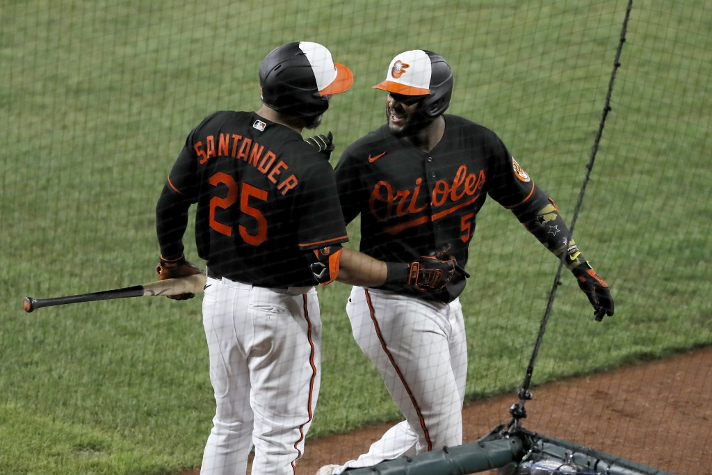 Baltimore Orioles' Hanser Alberto, right, talks with Anthony Santander (25) after hitting a solo home run off Tampa Bay Rays relief pitcher Ryan Thomp...