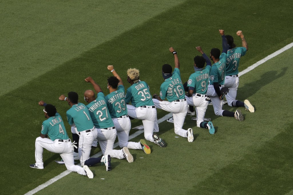 A group of Seattle Mariners players kneel together and raise their fists during a message about the Black Lives Matter movement before the Mariners' h...