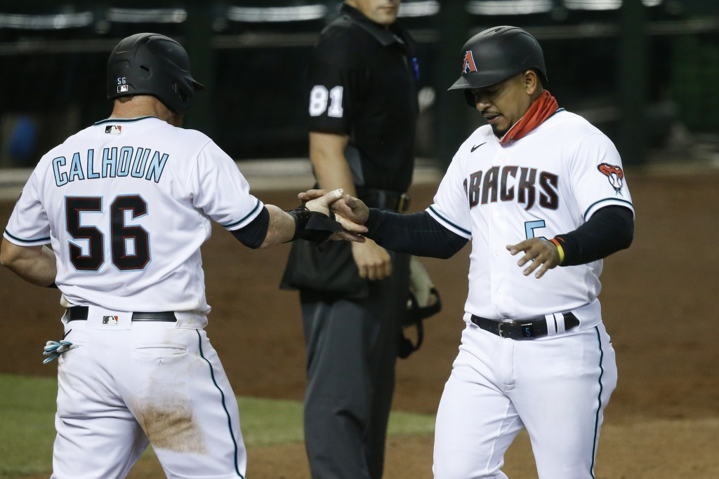 Arizona Diamondbacks' Kole Calhoun (56) and Eduardo Escobar, right, slap hands as they score runs against the Los Angeles Dodgers during the eighth in...