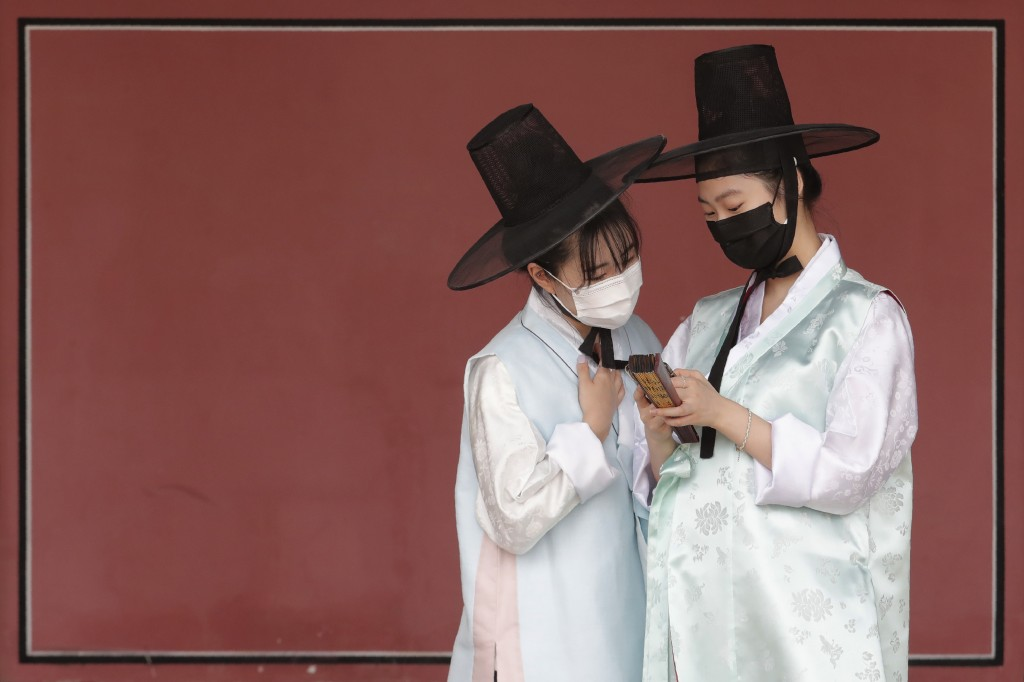 Women wearing traditional clothing and face masks to help protect against the spread of the new coronavirus look at a mobile phone at the Gyeongbok Pa...