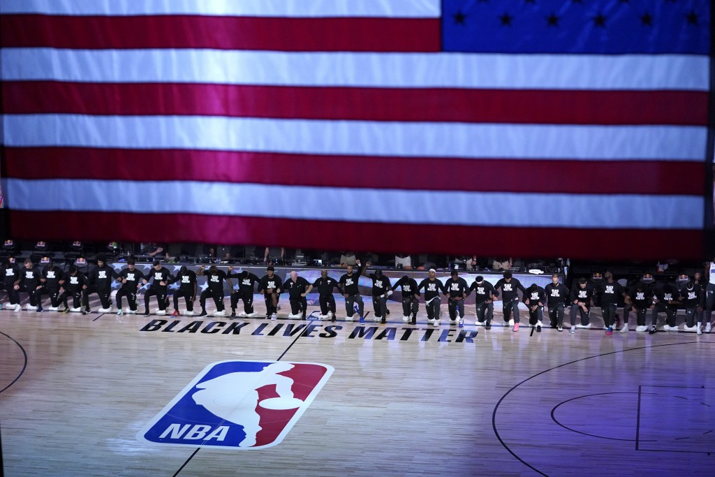 Members of the Orlando Magic and Brooklyn Nets kneel around a Black Lives Matter logo during the national anthem before the start of an NBA basketball...