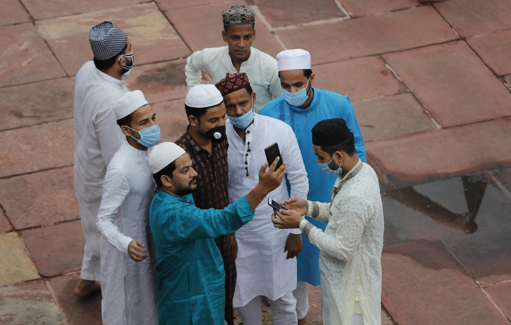 Indian Muslims take selfie after offering Eid al-Adha prayer at the Jama Masjid in New Delhi, India, Saturday, Aug.1, 2020. Eid al-Adha, or the Feast ...