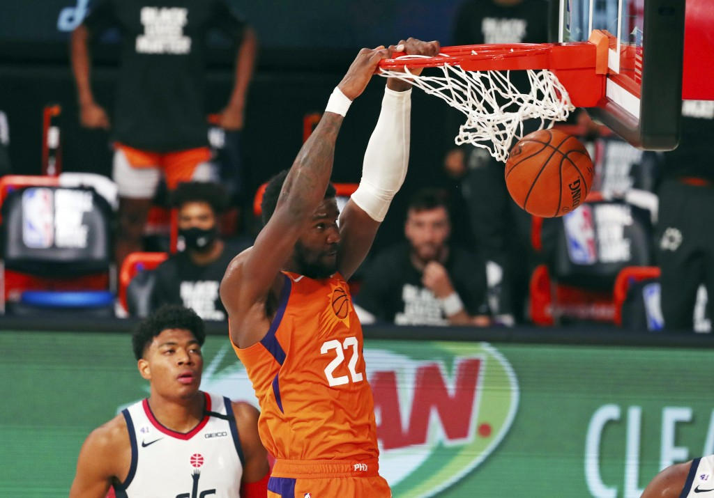 Phoenix Suns center Deandre Ayton (22) dunks the ball as Washington Wizards forward Rui Hachimura looks on during the second half of an NBA basketball...