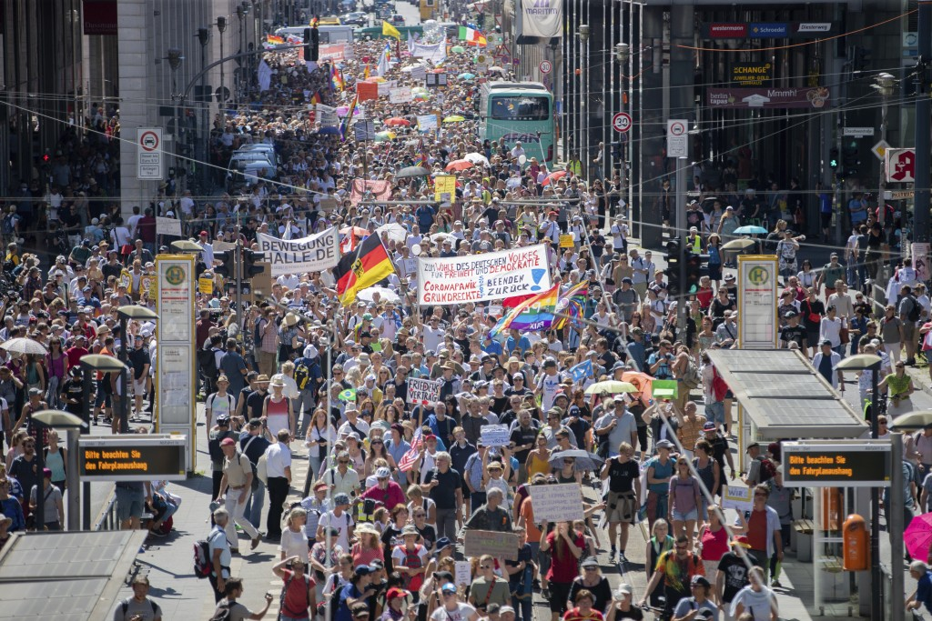 Thousands march along the 'Friedrichstrasse' during the demonstration against corona measures in Berlin, Germany, Saturday, Aug. 1, 2020. The initiati...