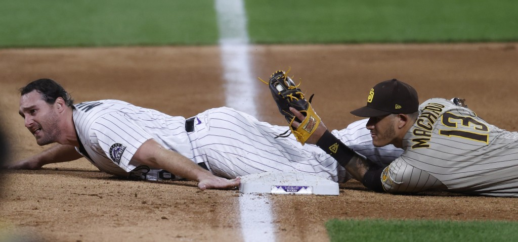 San Diego Padres third baseman Manny Machado, right, holds up his glove to show that he tagged out Colorado Rockies' Daniel Murphy as he tries to adva...