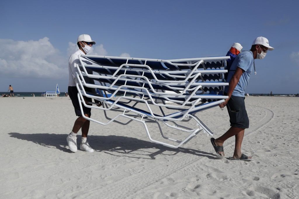 Workers remove chairs from the beach in preparation for Hurricane Isaias, Friday, July 31, 2020, in Miami Beach, Fla. Forecasters declared a hurricane...