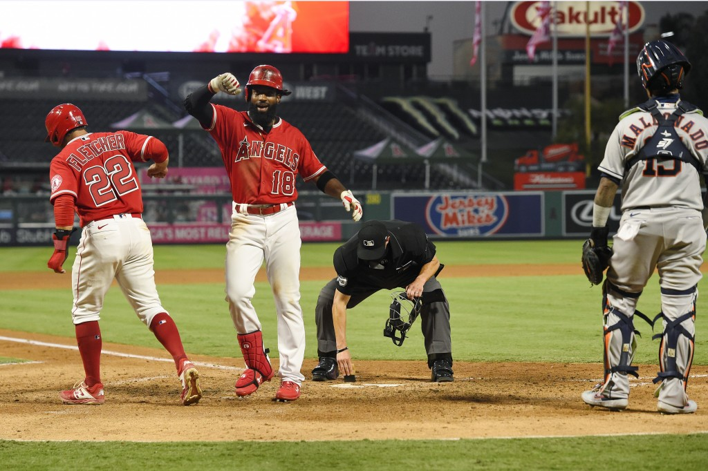 Los Angeles Angels' Brian Goodwin, second from left, is congratulated by David Fletcher, left, as Houston Astros catcher Martin Maldonado, right, stan...